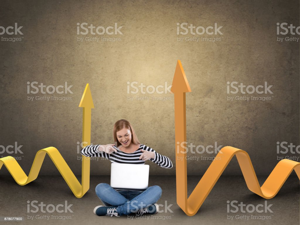 Woman celebrating success using laptop by graph stock photo