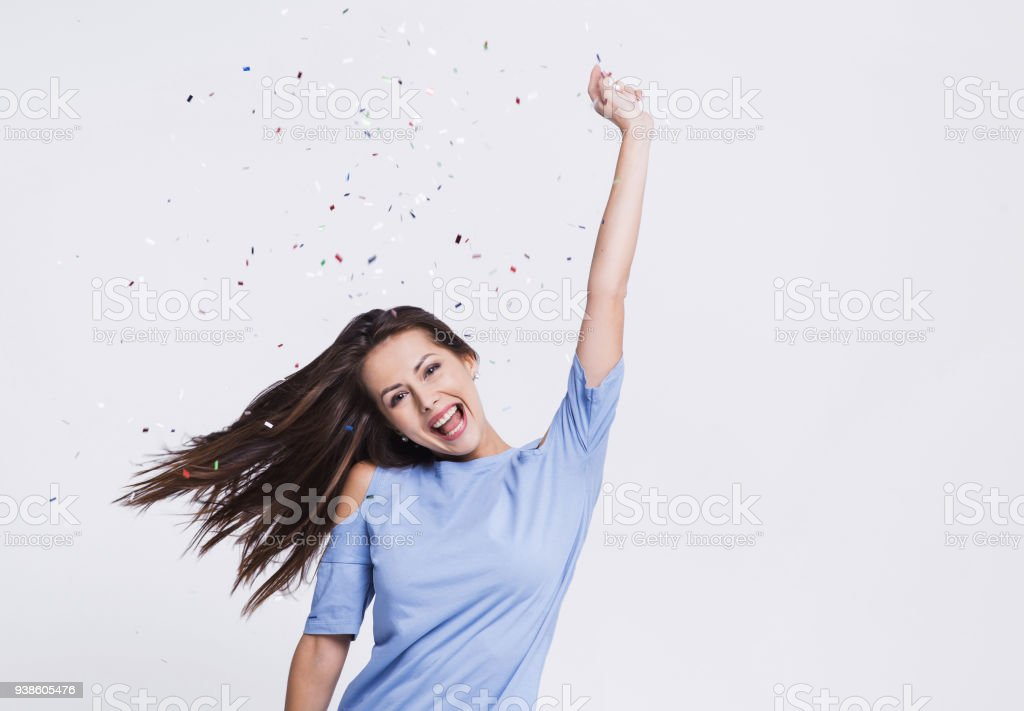 Woman celebrating success with falling confetti at party stock photo