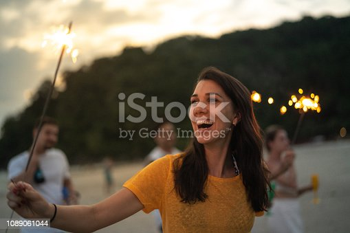 istock Woman celebrating the new year on the beach with sparkler 1089061044