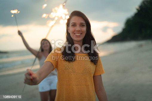istock Woman celebrating the new year on the beach with sparkler 1089409110