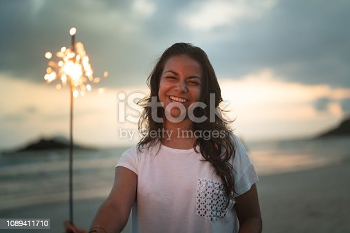 istock Woman celebrating the new year on the beach with sparkler 1089411710