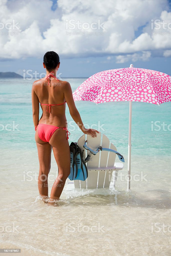woman, chair and umbrella at the beach stock photo