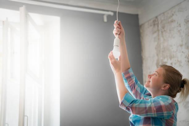 eine frau wechselt die lampe in der pendelleuchte. - glühbirne auswechseln stock-fotos und bilder