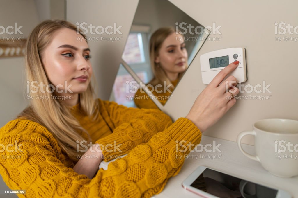 Woman changes the settings on a thermostat, central heating stock photo
