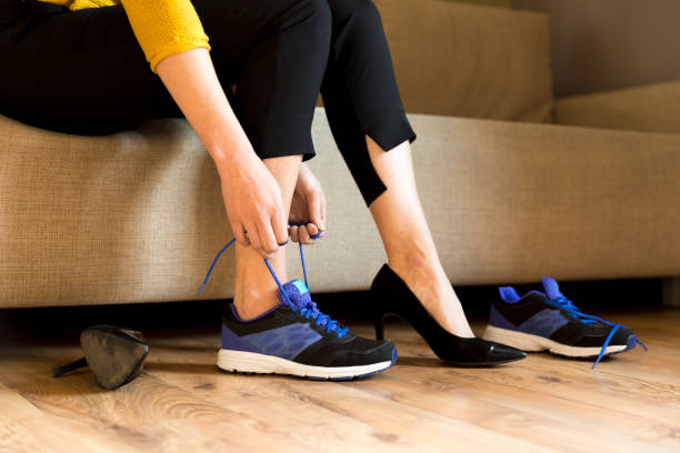 Woman changing high heels, office shoes after working day while sitting on the couch, ready to take a walk or run stock photo
