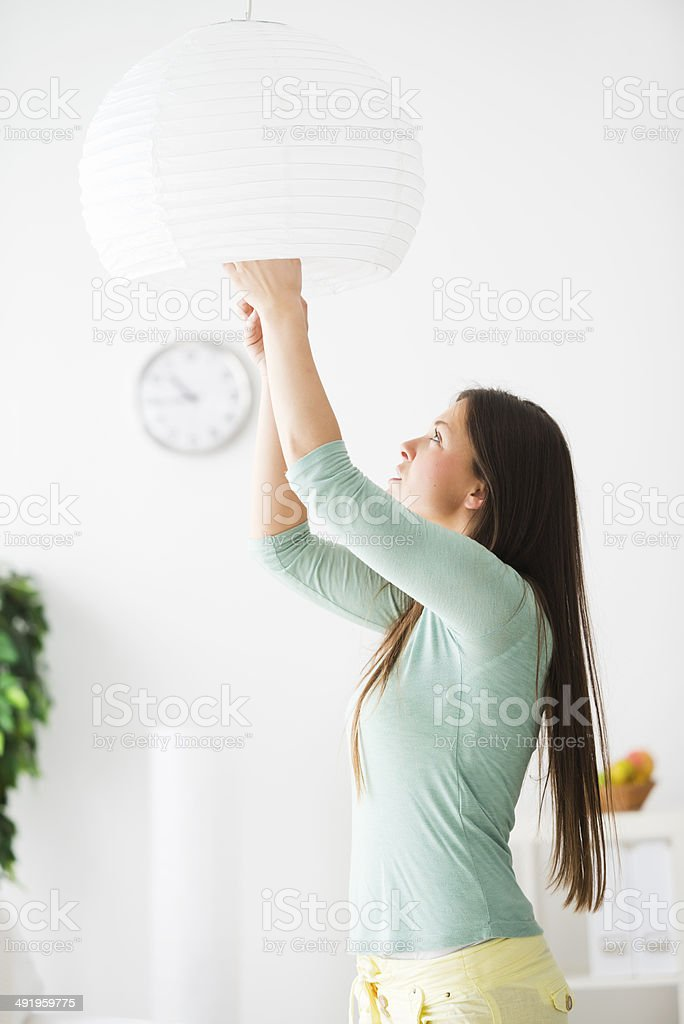 Woman changing light bulbs stock photo