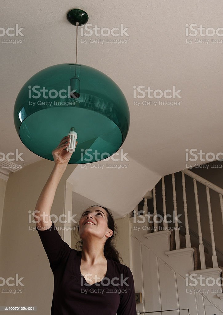 Woman changing lightbulb at home royalty-free stock photo