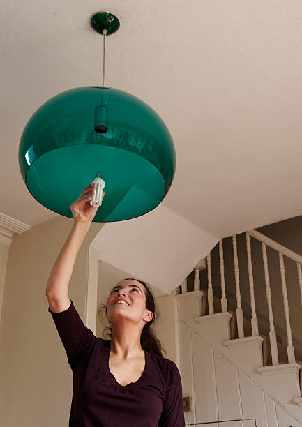 Woman changing lightbulb at home stock photo