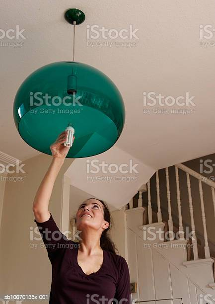 Woman Changing Lightbulb At Home Stock Photo - Download Image Now
