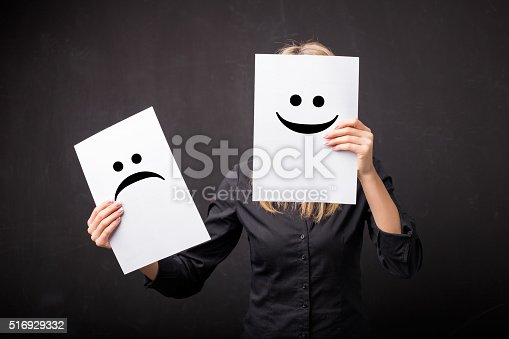 istock Woman changing smileys on her face 516929332