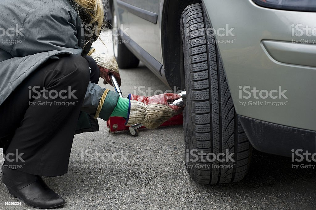 Woman changing tyres royalty-free stock photo