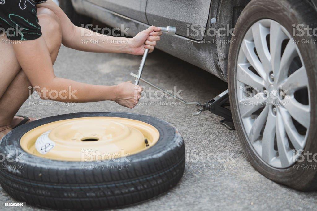 Woman changing wheel on a roadside stock photo