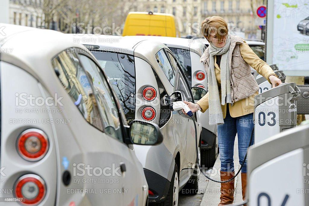 Woman charging Electric Car on Paris Street stock photo
