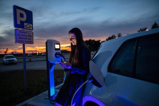 Woman charging her electric car on gas station at night. Woman using mobile phone while waiting for electric car to charge in the parking lot at night