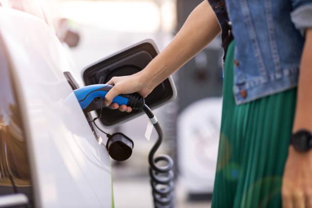 woman charging of an electric car - macchina ibrida foto e immagini stock