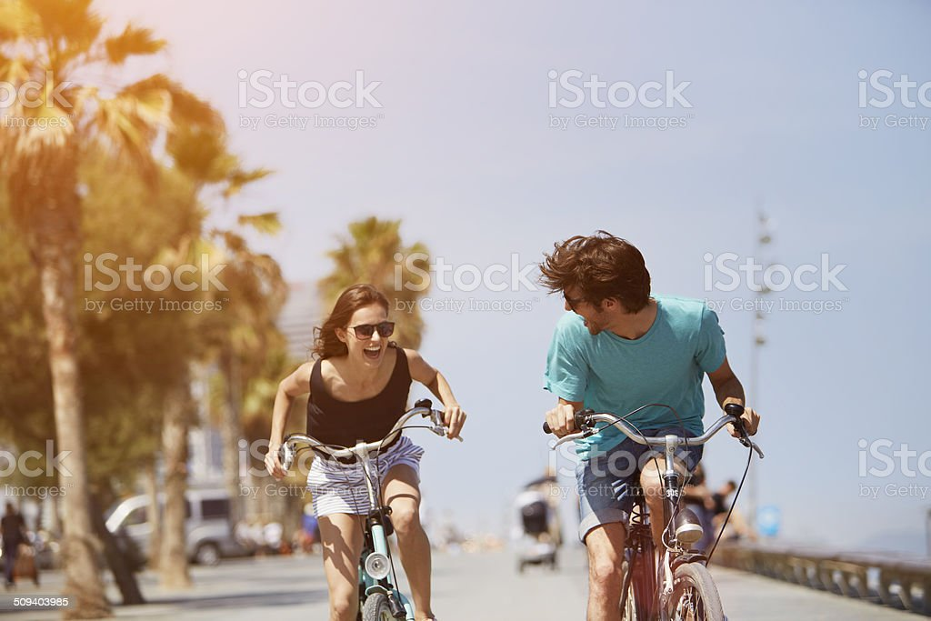 Woman chasing man while riding bicycle - foto de stock