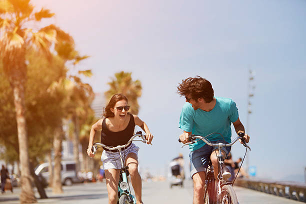 Woman chasing man while riding bicycle Happy young woman chasing man while riding bicycle during summer vacation barcelona spain stock pictures, royalty-free photos & images
