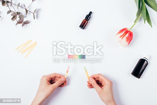 Woman check cosmetics pH level by using litmus paper and rating scale. Top view of female hands comparison reaction color on white background.