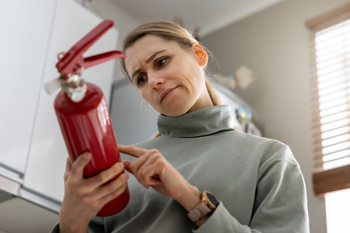 woman check the fire extinguisher expiration date at home