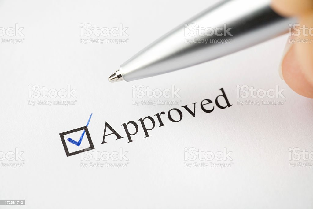Woman checking a box marked approved on a piece of paper royalty-free stock photo