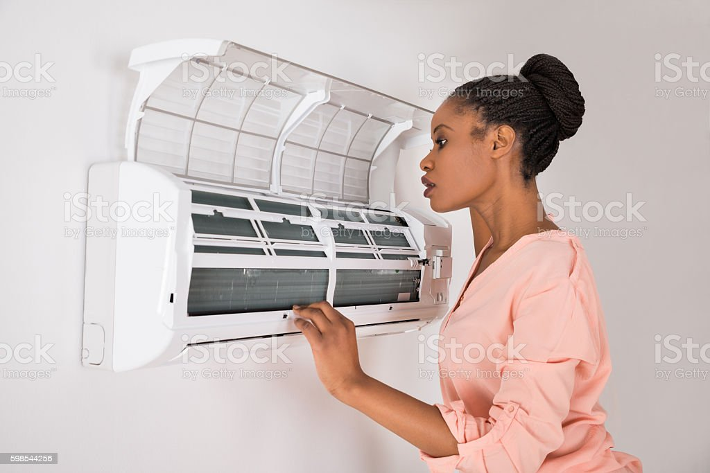 Woman Checking Air Conditioner stock photo
