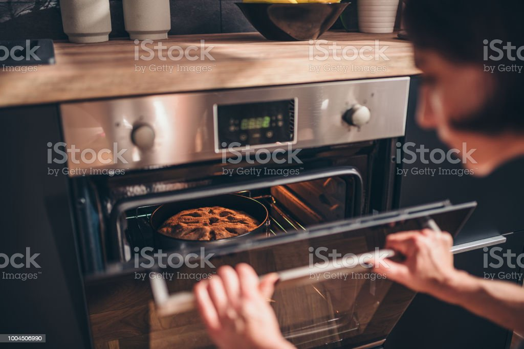 Woman checking apple pie in oven stock photo