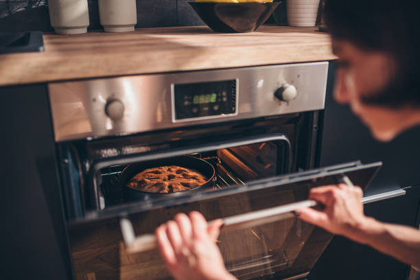 Woman checking apple pie in oven Woman standing by the oven and checking apple pie making a cake stock pictures, royalty-free photos & images