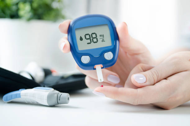 Woman checking blood sugar level by glucometer Diabetes checking blood sugar level. Woman using lancelet and glucometer at home. lancet arch stock pictures, royalty-free photos & images