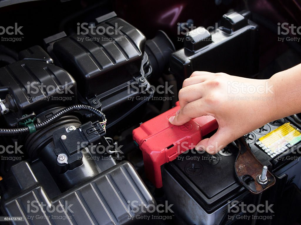 Woman checking car battery Parking on the street. stock photo