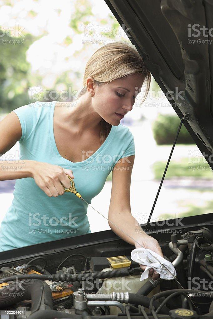 Woman checking car oil stock photo