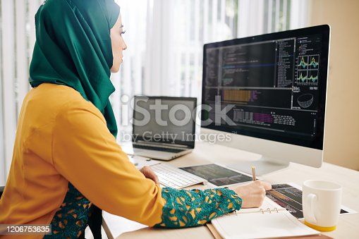 Young woman in hijab checking code implementation and taking notes in planner