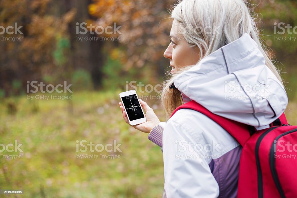 Woman checking compass app on her smartphone stock photo