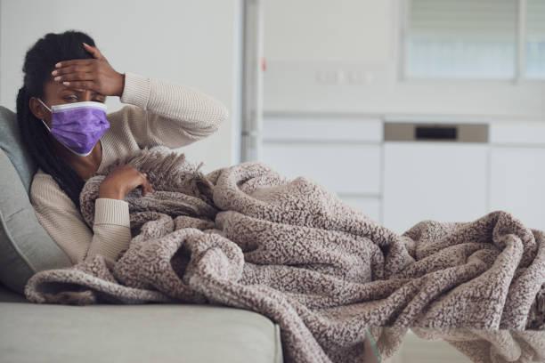 mujer revisando la fiebre. - síntoma fotografías e imágenes de stock