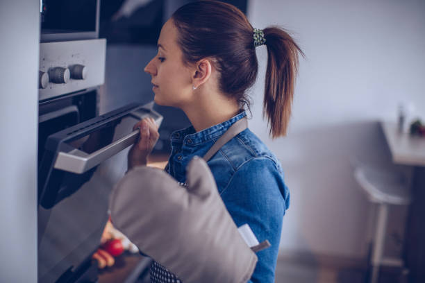 Woman checking food in the oven Woman checking food in the oven making a cake stock pictures, royalty-free photos & images