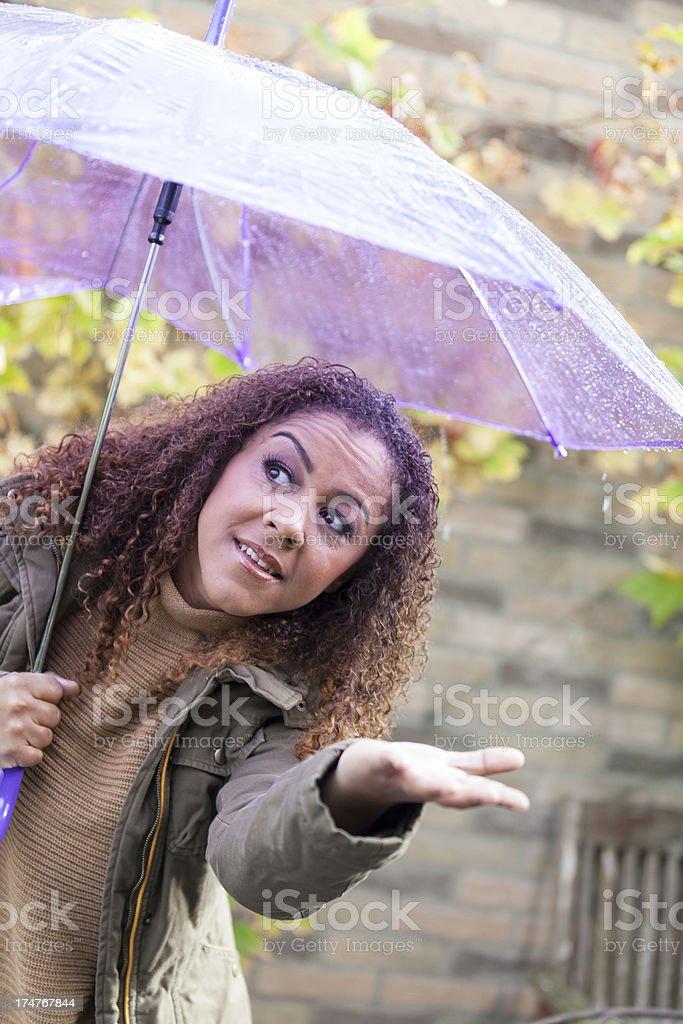 Woman checking for rain under umbrella stock photo