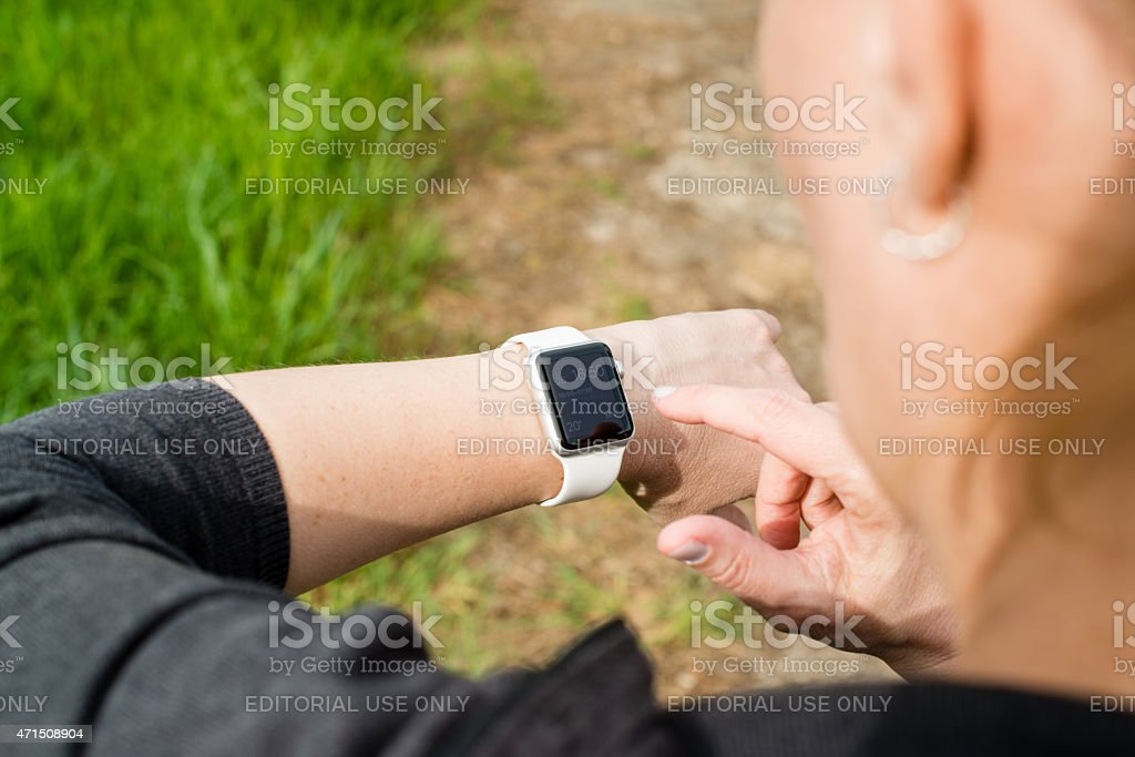 Woman checking her Apple Watch while walking stock photo
