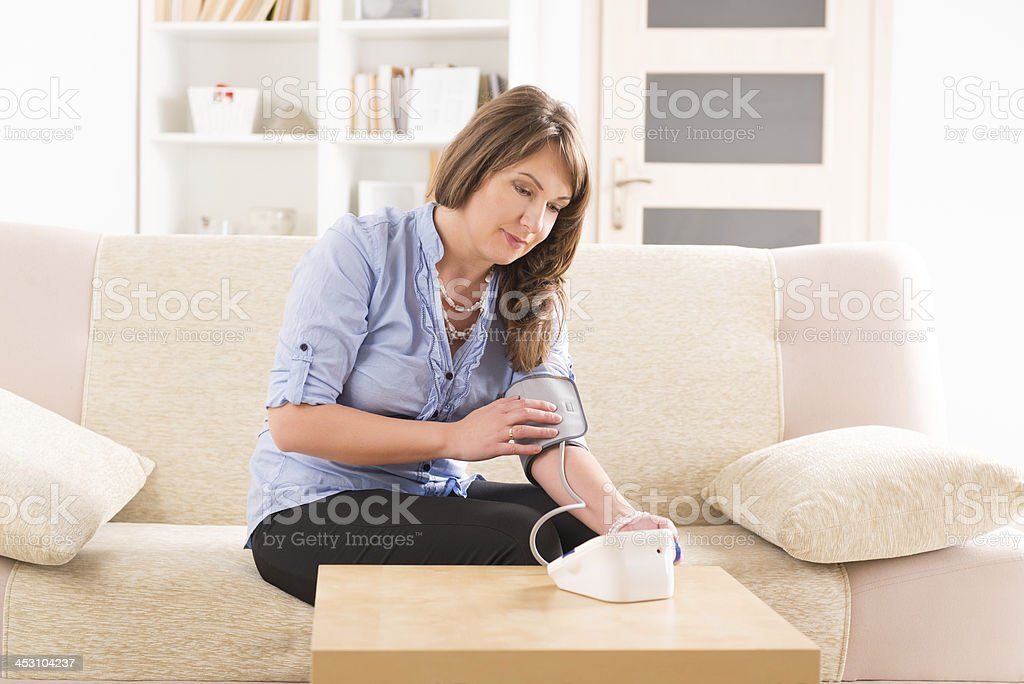 woman checking her blood pressure stock photo