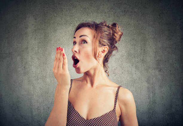 Woman checking her breath with hand. stock photo