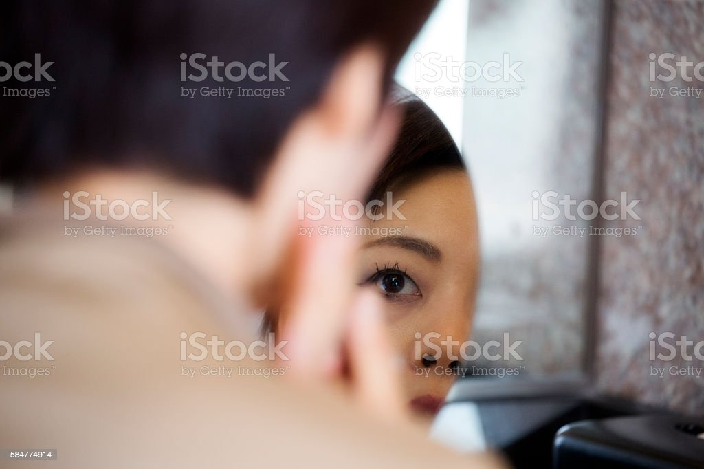 Woman checking her face in the mirror foto