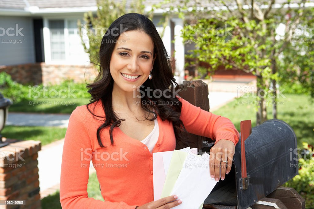 Woman checking her mailbox and smiling royalty-free stock photo