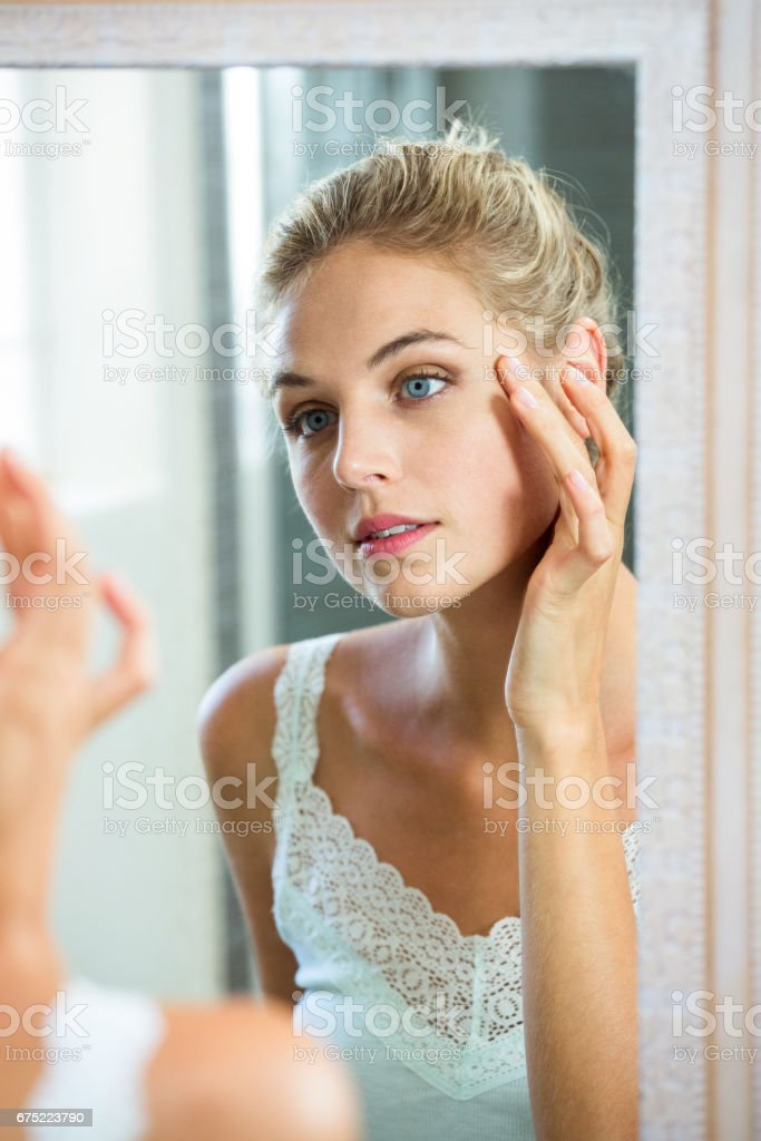 Woman checking her skin in bathroom royalty-free stock photo