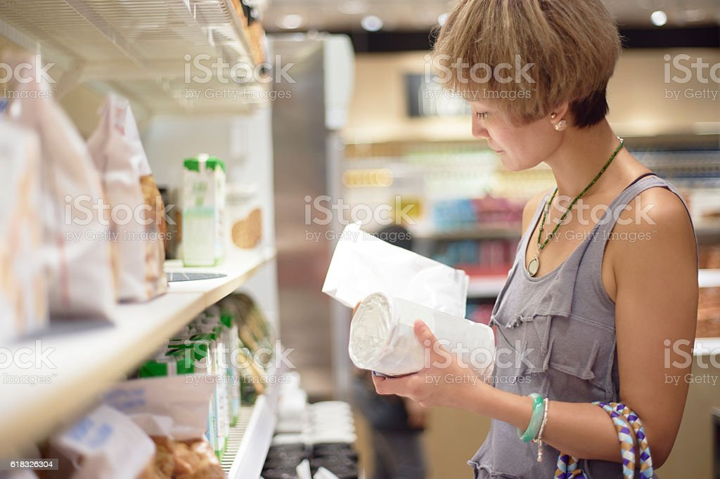 woman checking info on package in supermarket stock photo