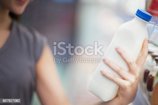 Woman checking label on milk in supermarket dairy section