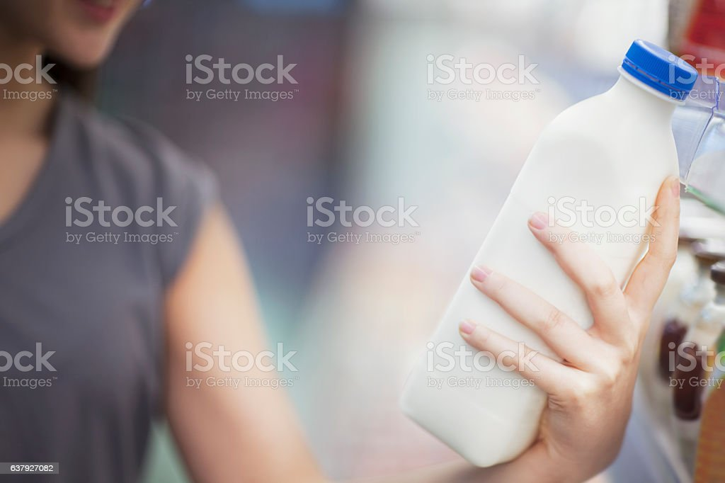 Woman checking label on milk in supermarket dairy section stock photo