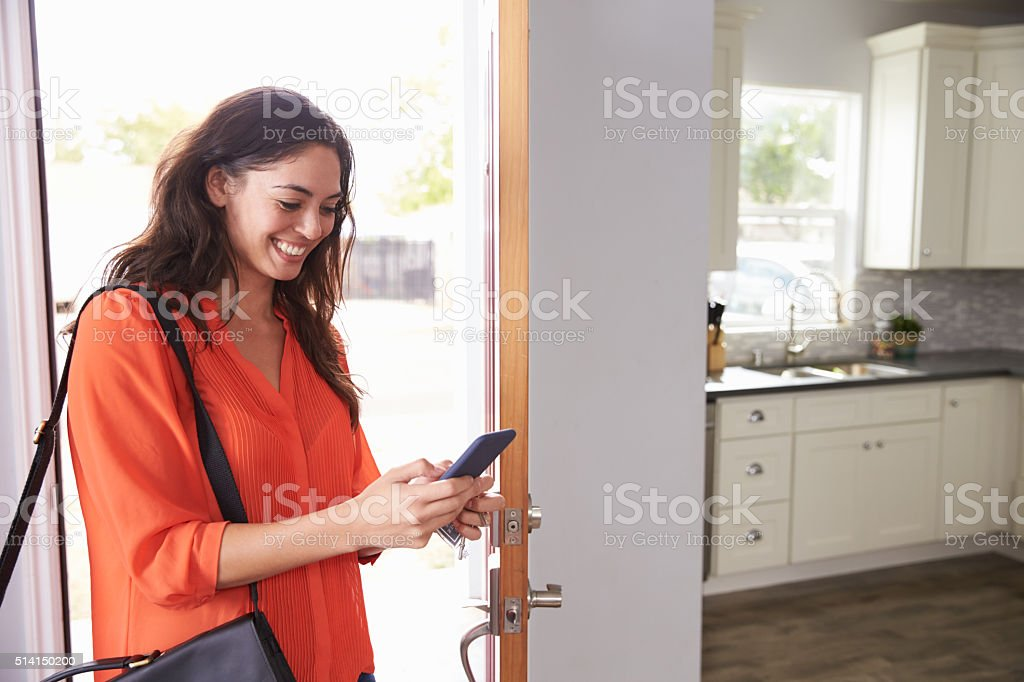 Woman Checking Mobile Phone As She Opens Door Of Apartment stock photo