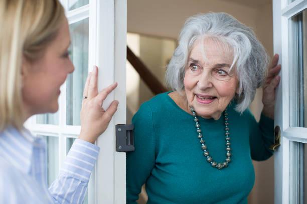 woman checking on elderly female neighbor - vicino foto e immagini stock