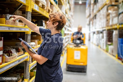 Woman with checklist picking jar from package on warehouse rack