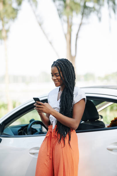 Woman checking phone before driving stock photo