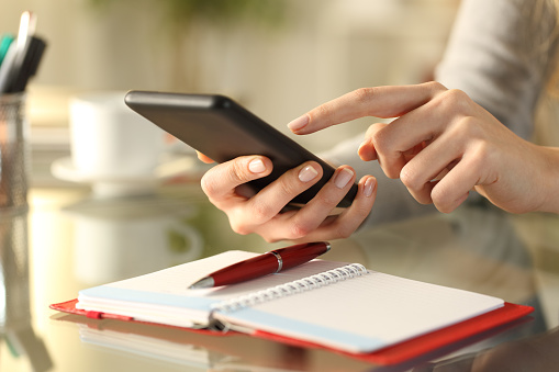 Close up of woman hands checking smart phone with personal organizer diary or agenda over the table at home