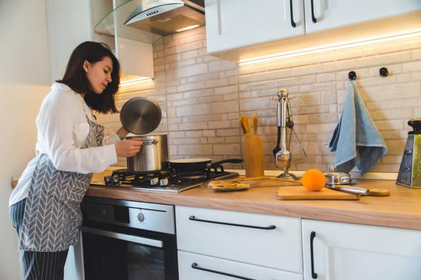 frau prüft topf mit kochendem wasser in der küche - chefkoch auflauf stock-fotos und bilder